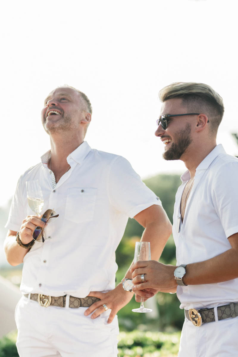 Grooms wearing white jeans and shirts laughing at the speeches on their wedding day