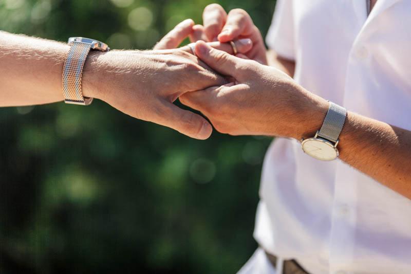 Gay men exchanging platinum wedding rings