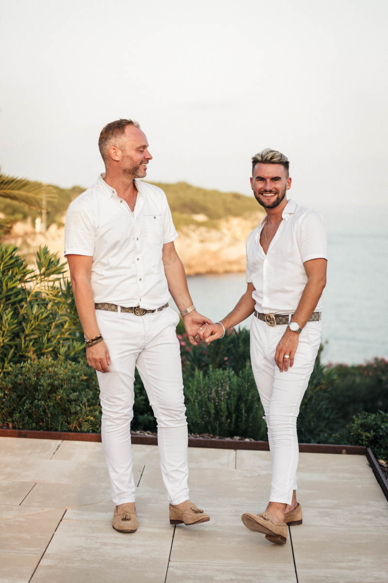 Gay men holding hands for their wedding day portraits over looking the sea in Sitges