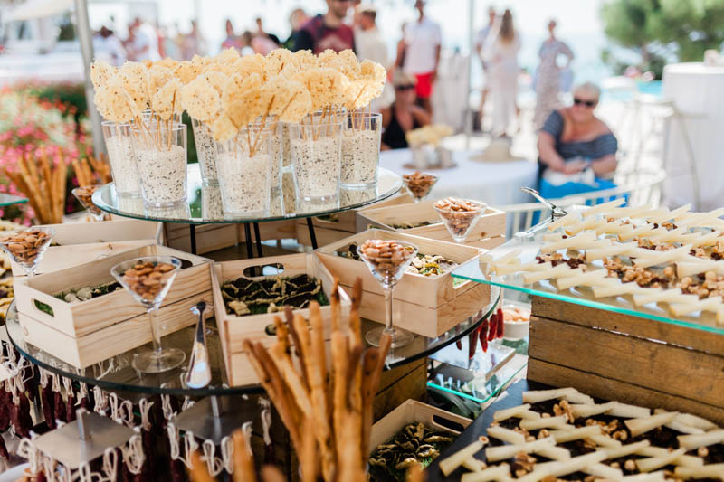 Almonds in boxes and cheese sticks in glasses at Masia Casa Del Mar wedding
