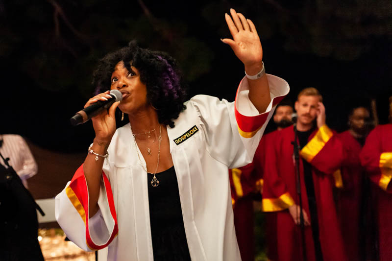 Gospeloke lead vocalist wearing white gown and holding microphone