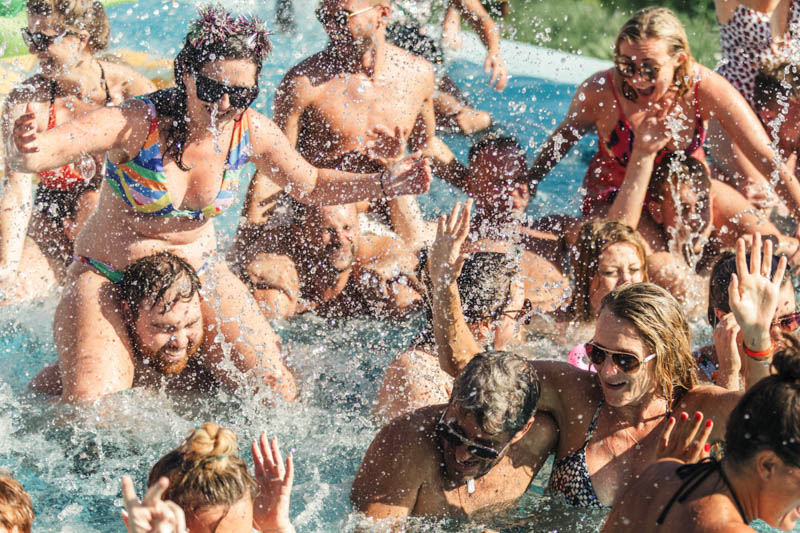 Lots splashing in the pool with guests at the wedding day pool party