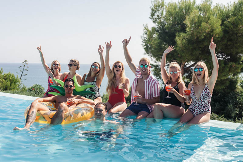 Guests chilling in the pool sitting on inflatable palm tree at Masia Casa Del Mar in Sitges