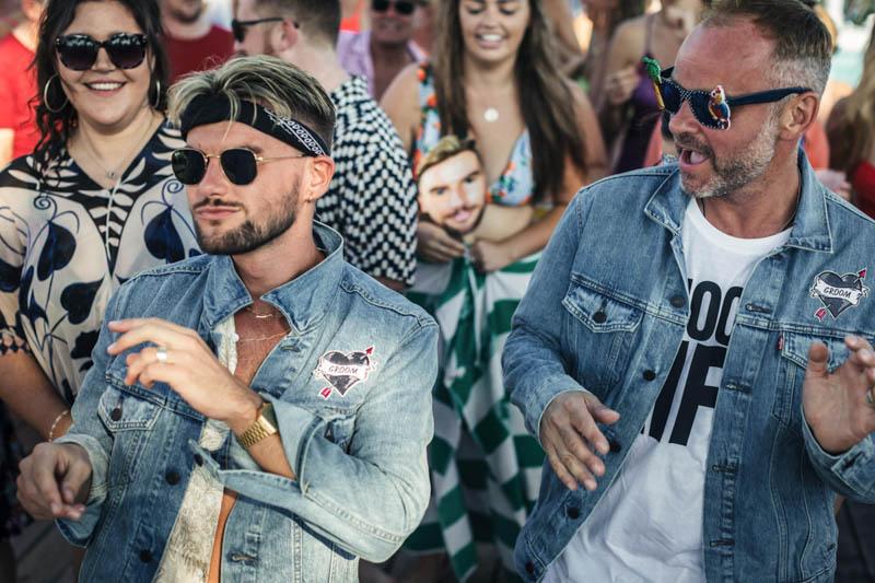 Grooms dancing wearing denim jackets and ray-ban sunglasses at Masia Casa del mar wedding