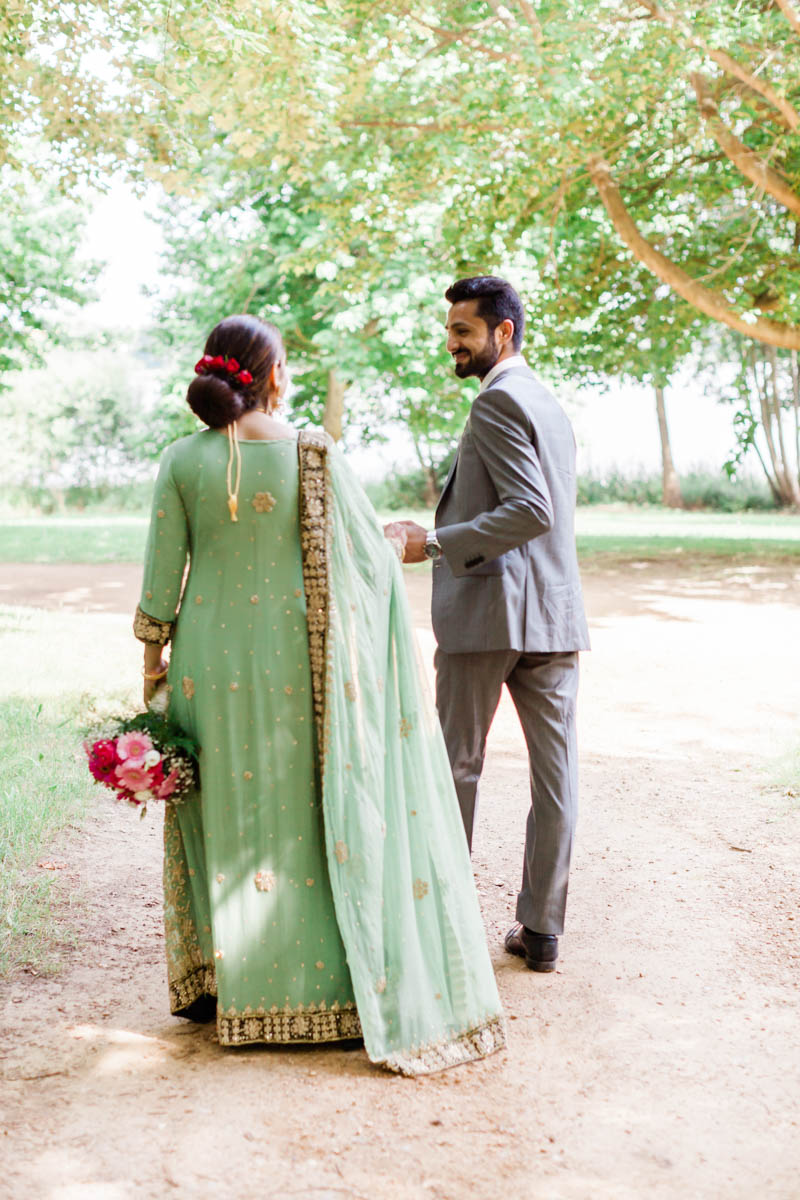 Indian woman wearing long green and gold dress holding bouquet of pink flowers at her engagement session