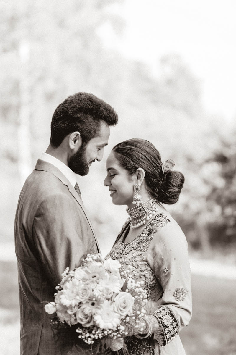 Elegant romantic portrait of Indian engagement session looking at each other and smiling holding her bouquet of pink roses