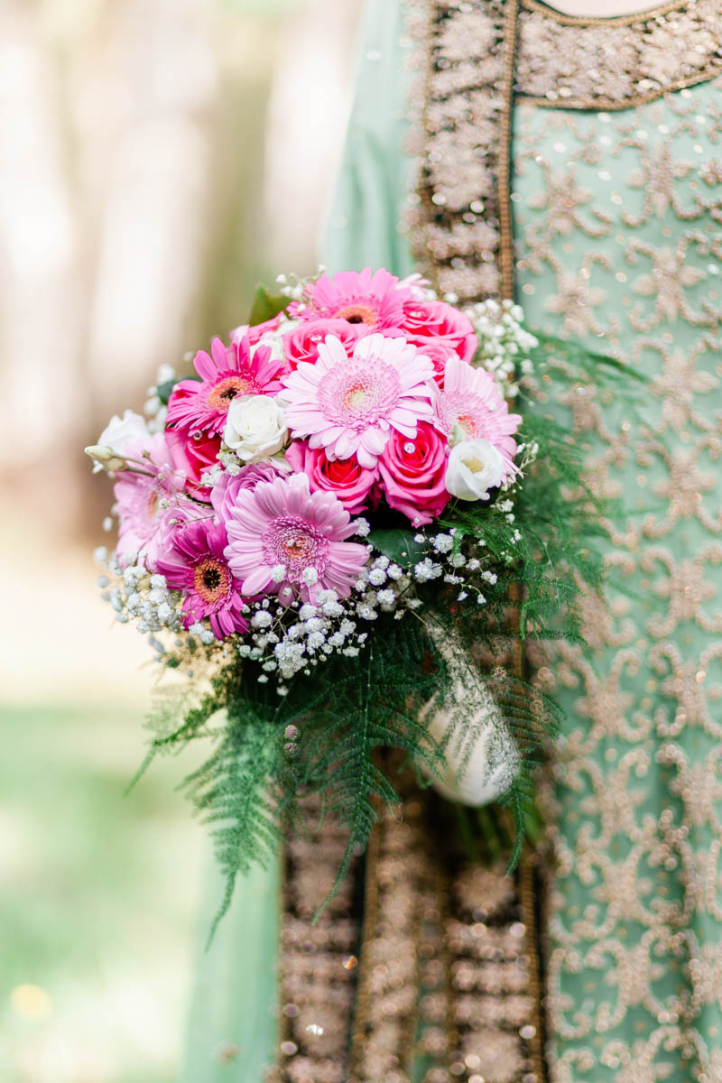 Close up of a bright pink and white wedding bouquet hand tied with green ribbon and dotted with jewels