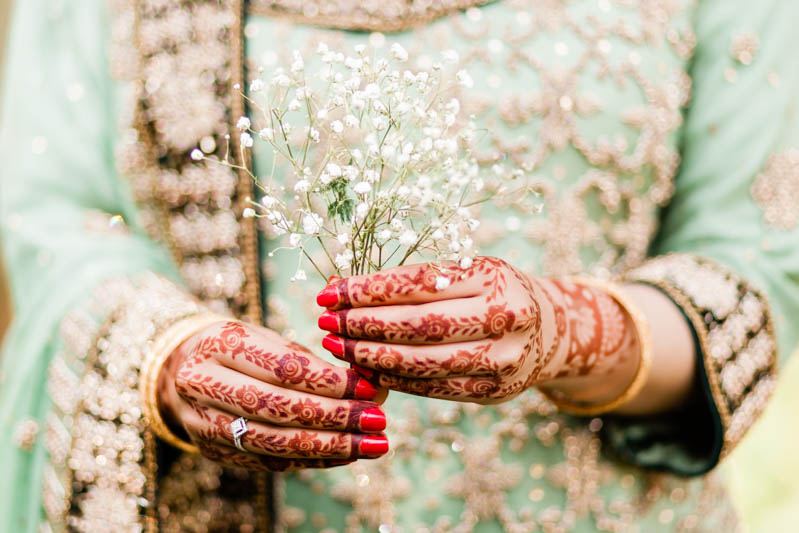 elegant hands decorated with henna and red nail varnish holding a flower on engagement shoot at Virginia water lake in Surrey