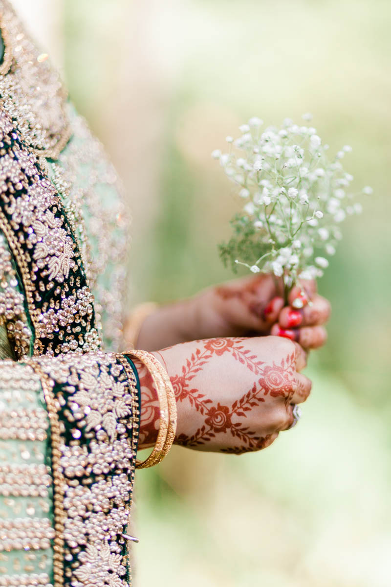 Close up of henna design on woman hands holding a flower against a backdrop of green bushes