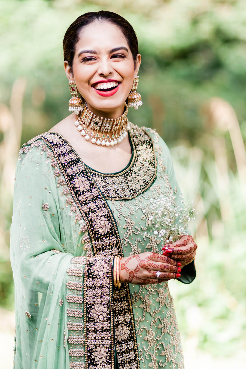 Woman giggles on her engagement session showing off her henna hand paint and beautiful diamond engagement ring