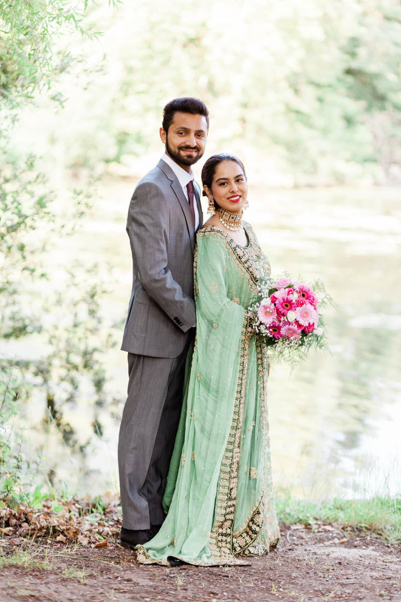 formal portrait of newly engaged couple standing against the backdrop of Virginia water lake Surrey
