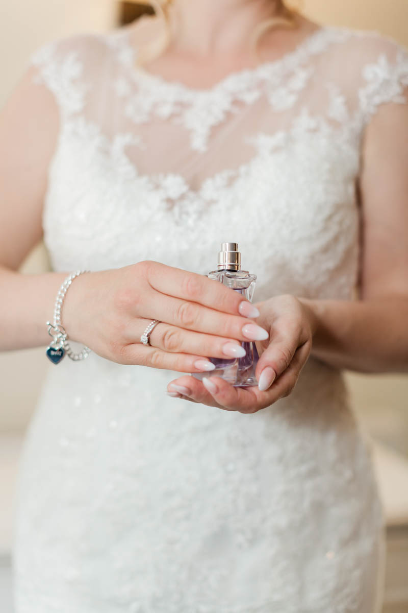 Bride holding her wedding day perfume bottle and showing her engagement ring at Sopley Mill