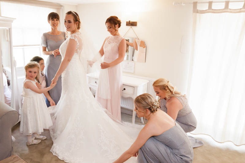 Five bridesmaids help the bride get into her dress in the bridal suite at Sopley Mill Dorset
