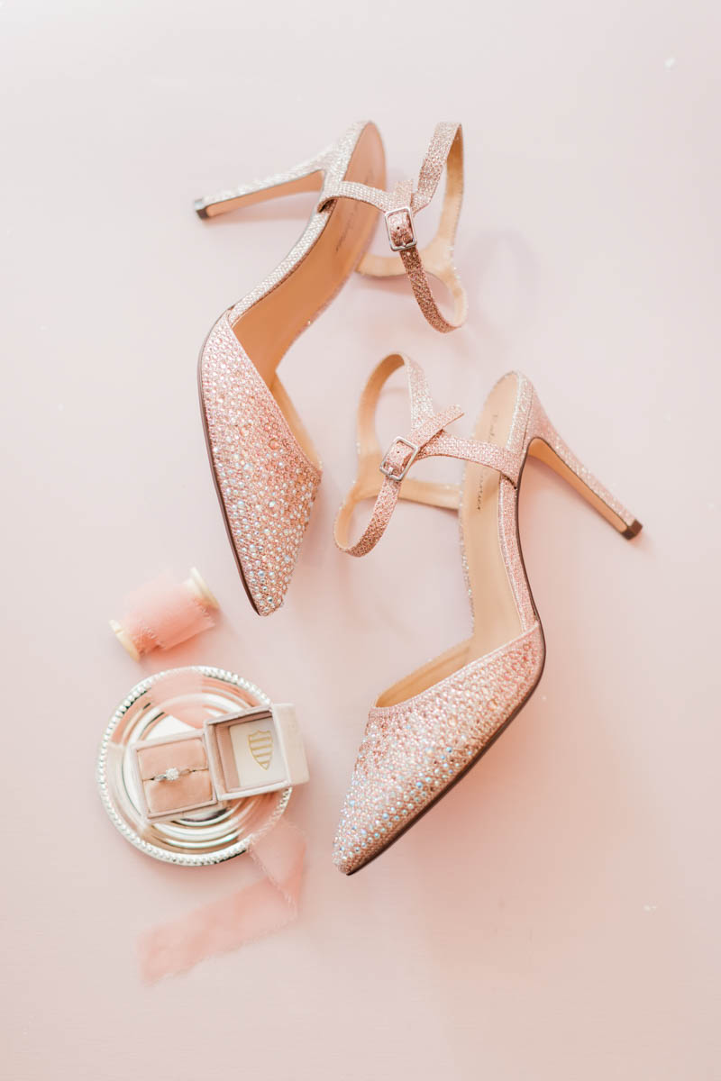Roland Cartier wedding shoes on a pink background with engagement ring in pink velvet ring box