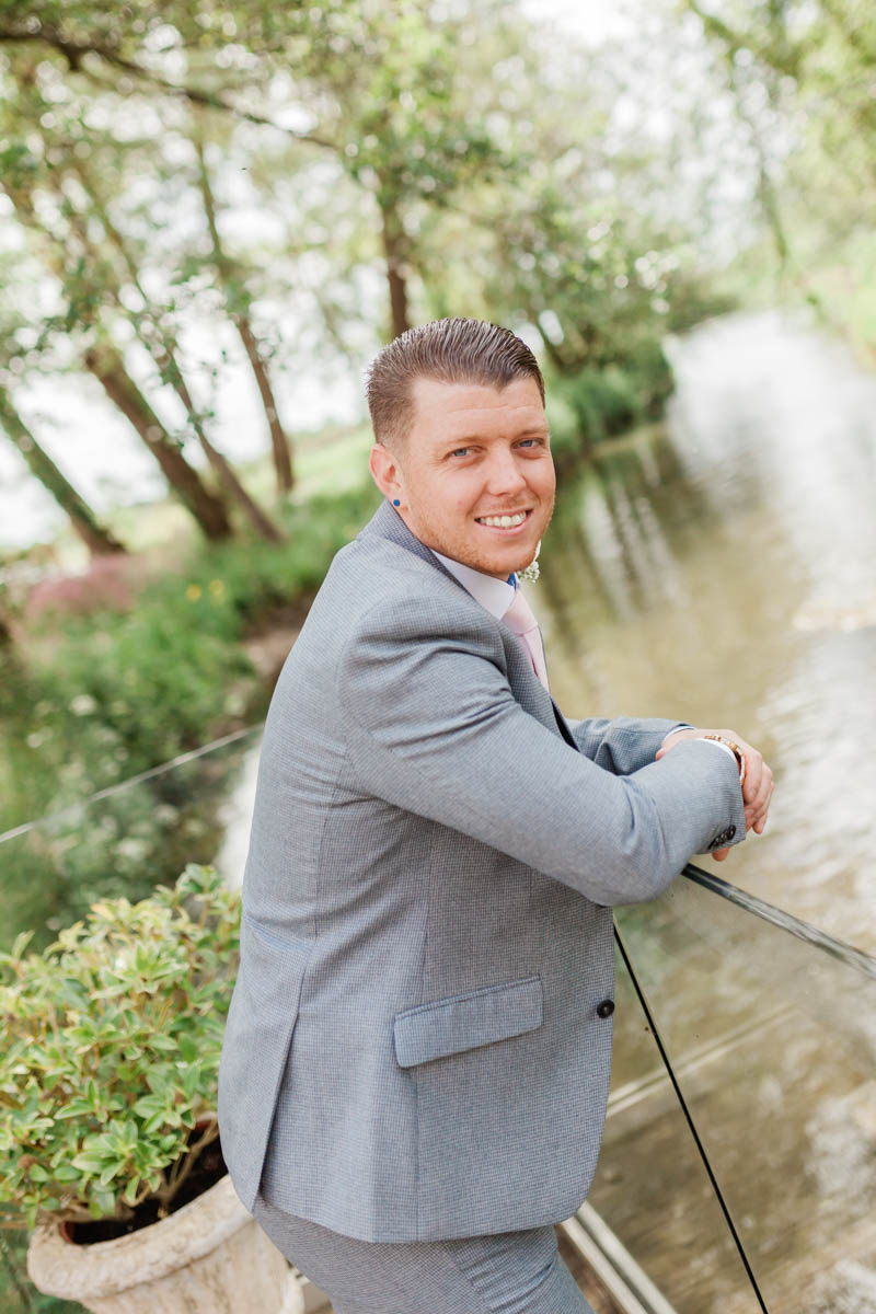 Portrait of groom stood by the river at Sopley mill in Dorset