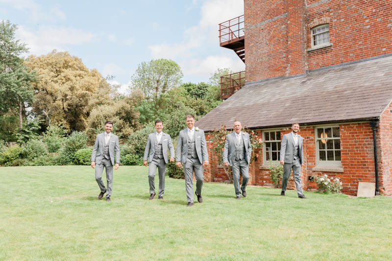 Groom and best man walking through the garden at the front of Sopley Mill in Dorset