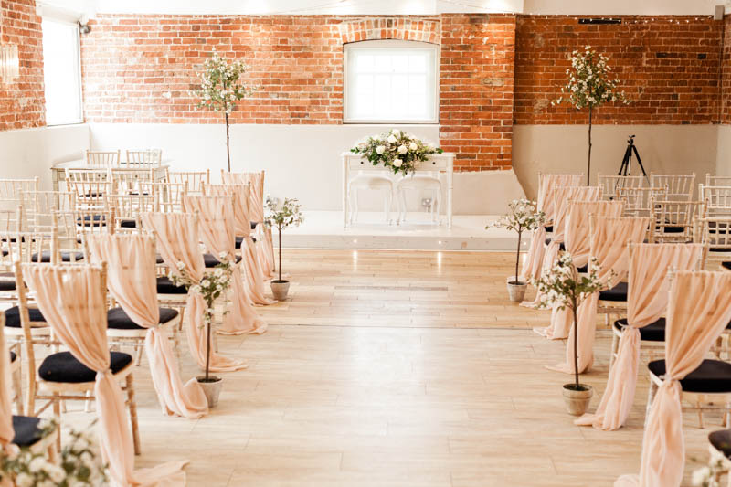 ceremony room decorated with pale pink chair covers at Sopley Mill in Dorsetbride and groom kiss eachother at the alter of the cerony