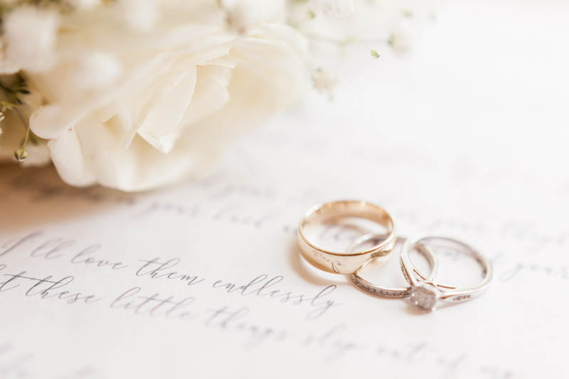 Wedding rings placed on lyrics to first dance song with a white rose