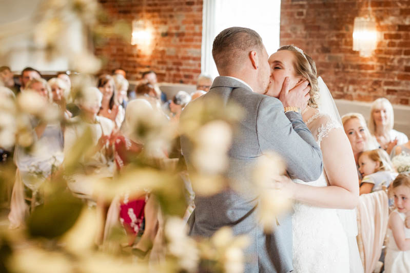 bride and groom kiss each other at the altar of the ceremony at Sopley Mill in Dorset