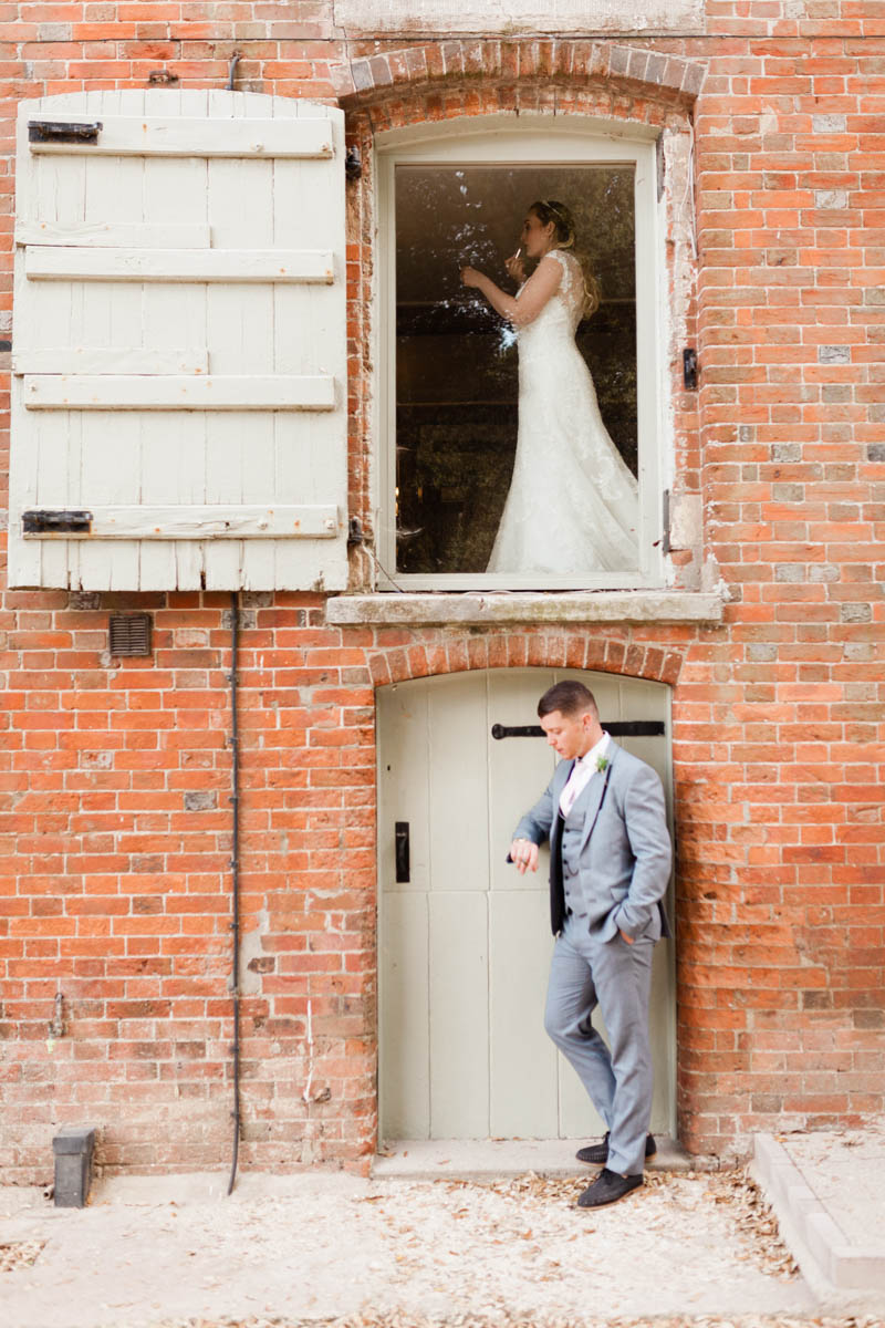 Bride getting ready with the groom waiting underneath the window looking at his watch outside solely mill