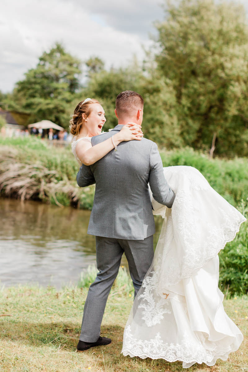 Groom sweeps bride off her feet in the ground overlooking Sopley Mill in Dorset