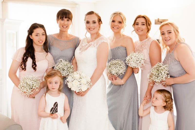 Bridesmaids portrait holding white roses bouquets