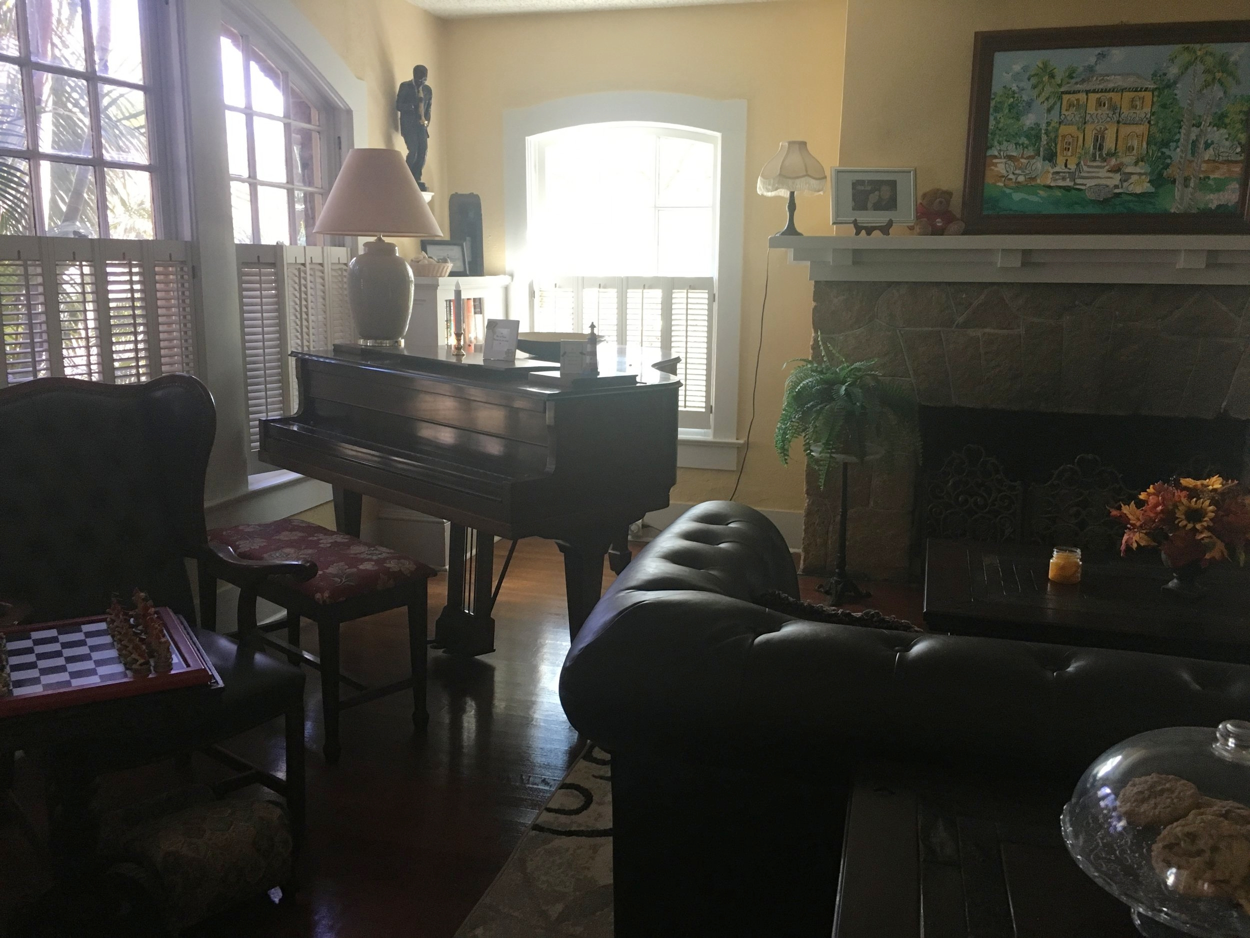 Cookies sat on a covered platter in the sitting area behind a couch that faced the fireplace, a piano rested in the corner of the room, and a door on the opposite side led to a sunroom.