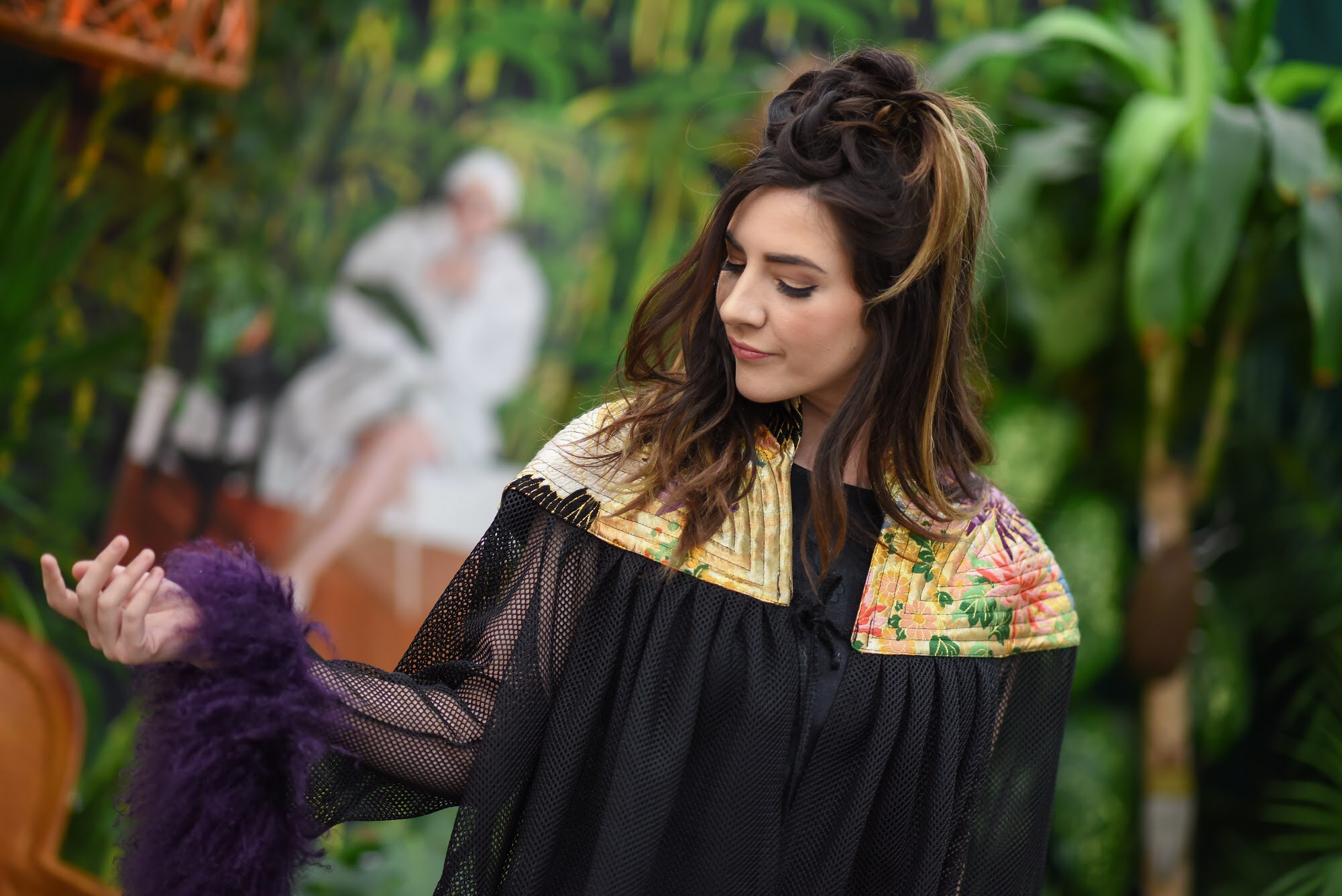 Model  Julianne Selke  wearing  Susan Bradley . I picked a rich looking garment that would pop against Hilton's green jungle. The jewel tones in the shoulders of the caplet add a bursts of bright colors and the fuzzy, alpaca-trimmed, mesh sleeves give a textural contrast to the vegetation. Hair by  Sherri Renee , makeup by  Ariel Lewis .