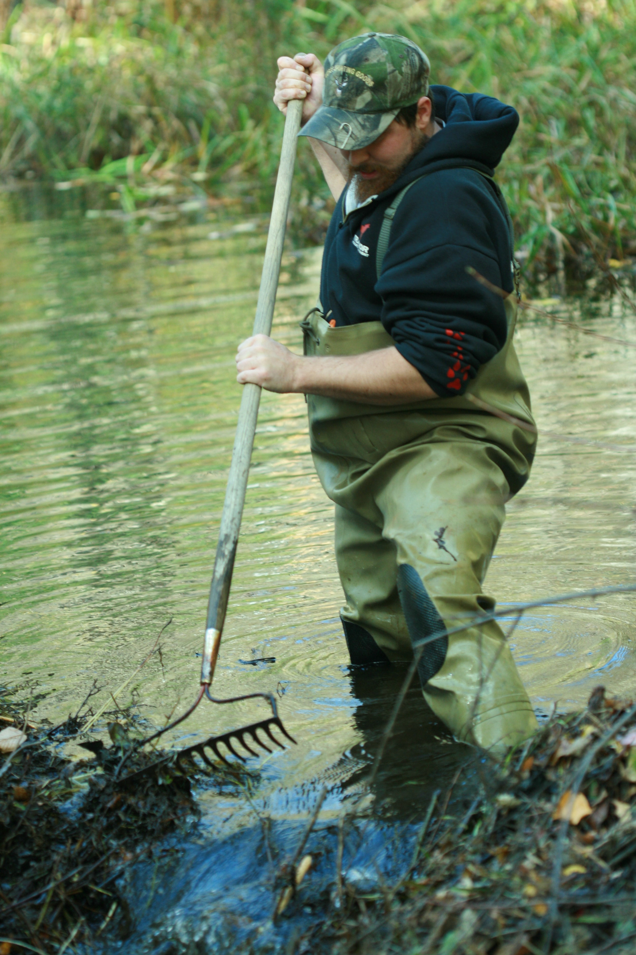 The author removes a section of beaver dam along a flooded driveway. (Photo | Furbearer Conservation)