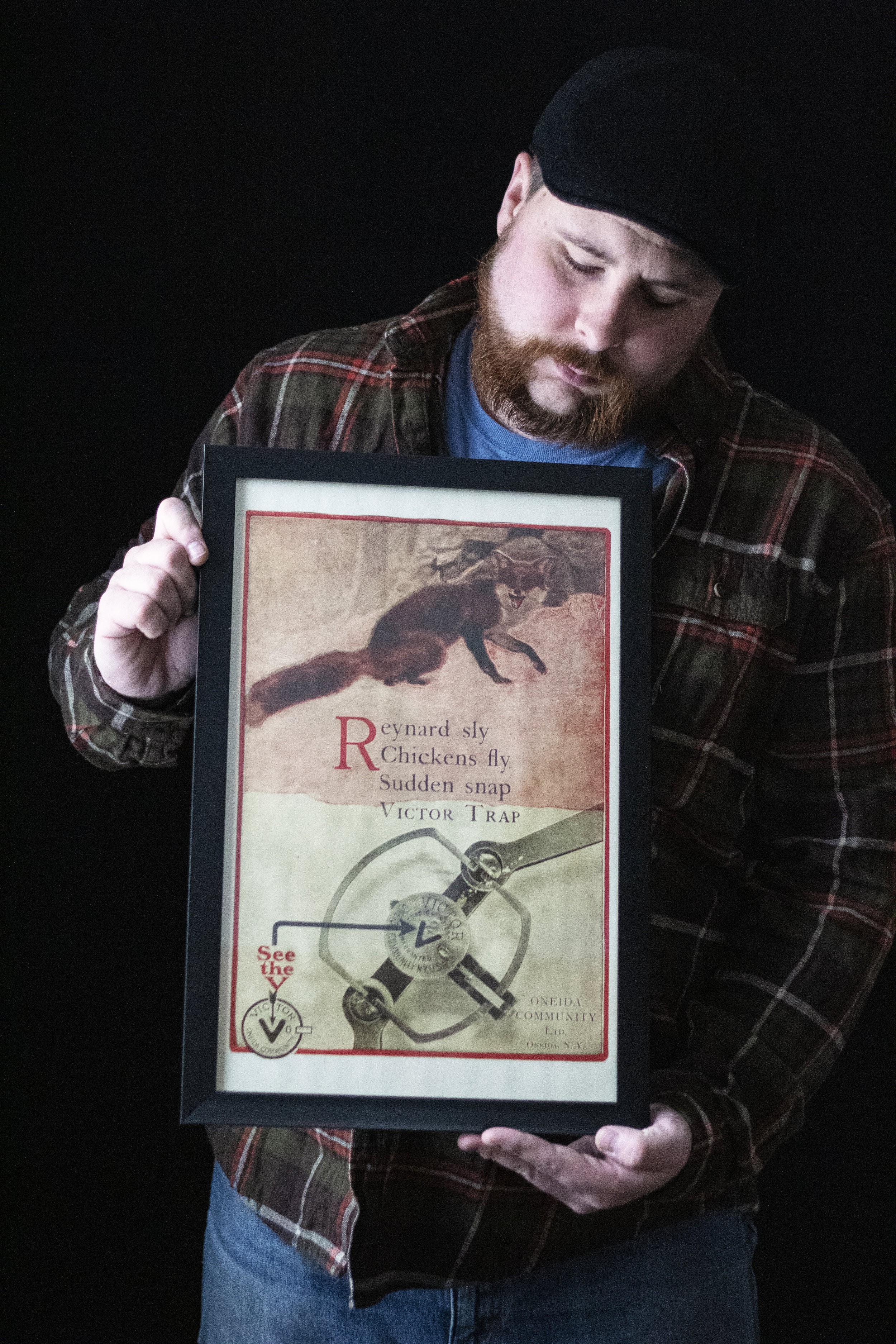 The author with a vintage trap advertising print. (Photo | Furbearer Conservation)
