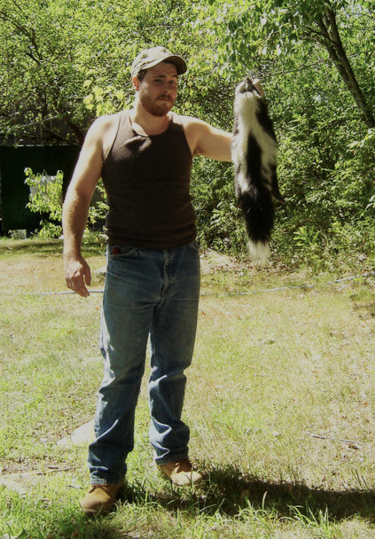 A young Jeff Traynor with an even younger striped skunk, after retrieving the animal's remains from the private well of a local client. (Photo | Furbearer Conservation)