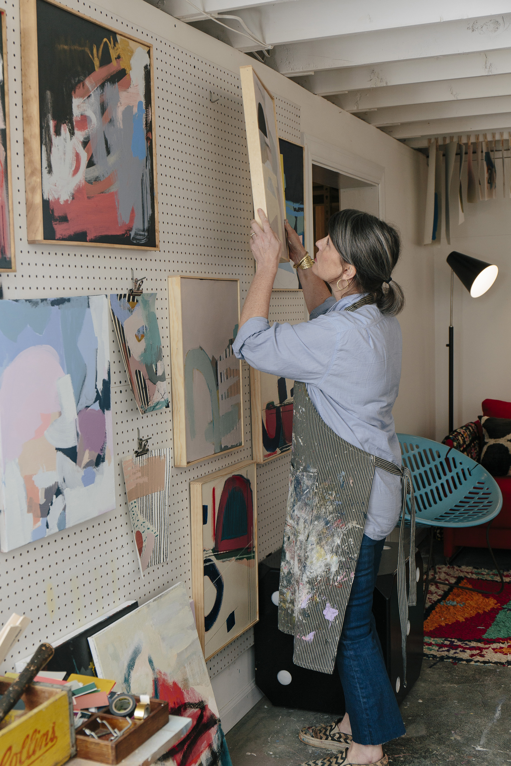 Jenny, hanging original work on her display wall. All her paintings and frames are made by hand in her vibrant, eclectic home studio. Find her work at  Jenny Prinn  or at  Serena & Lily .
