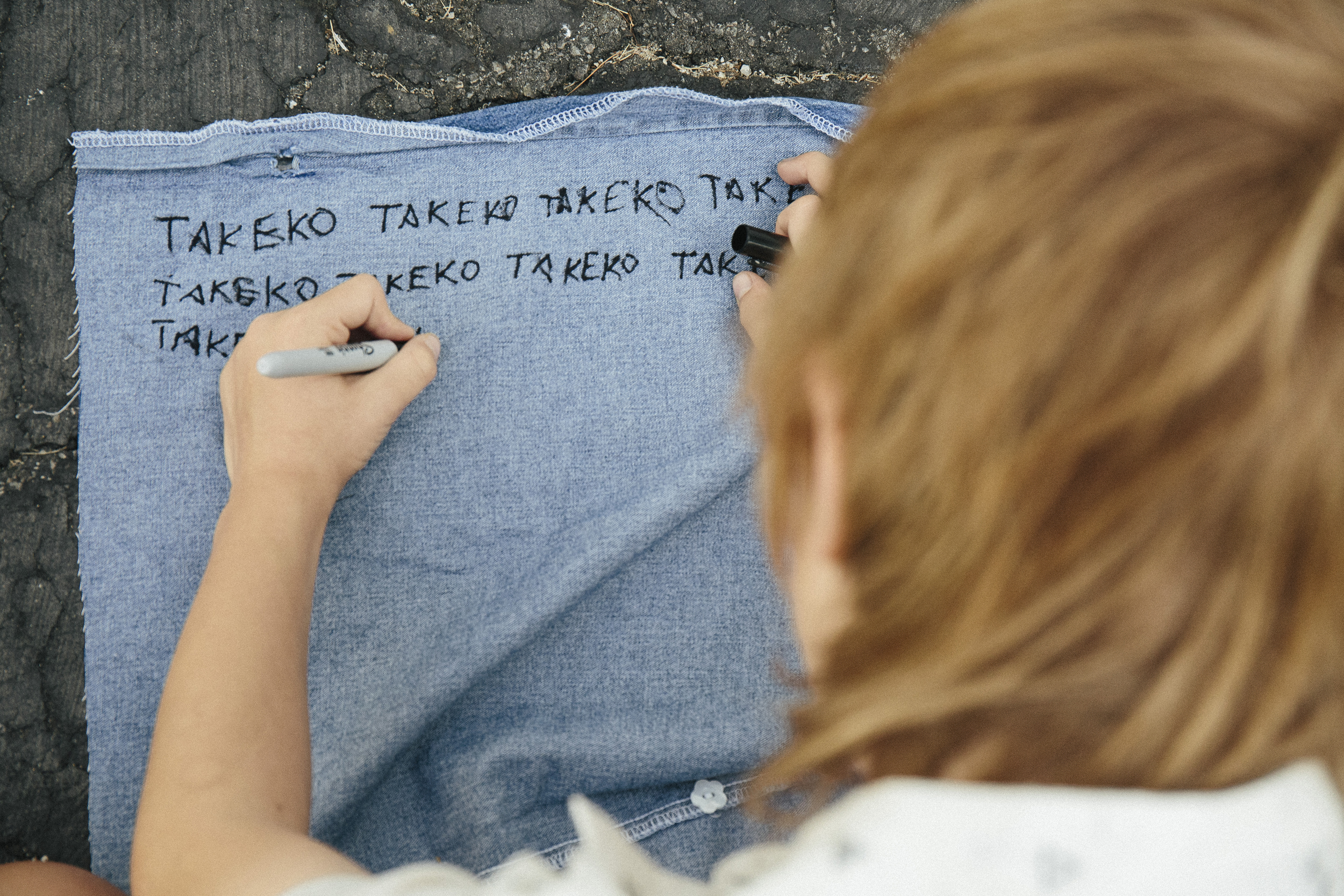 Laura Ker's son Connor hand draws TAKEKO labels that are sewn onto each design.