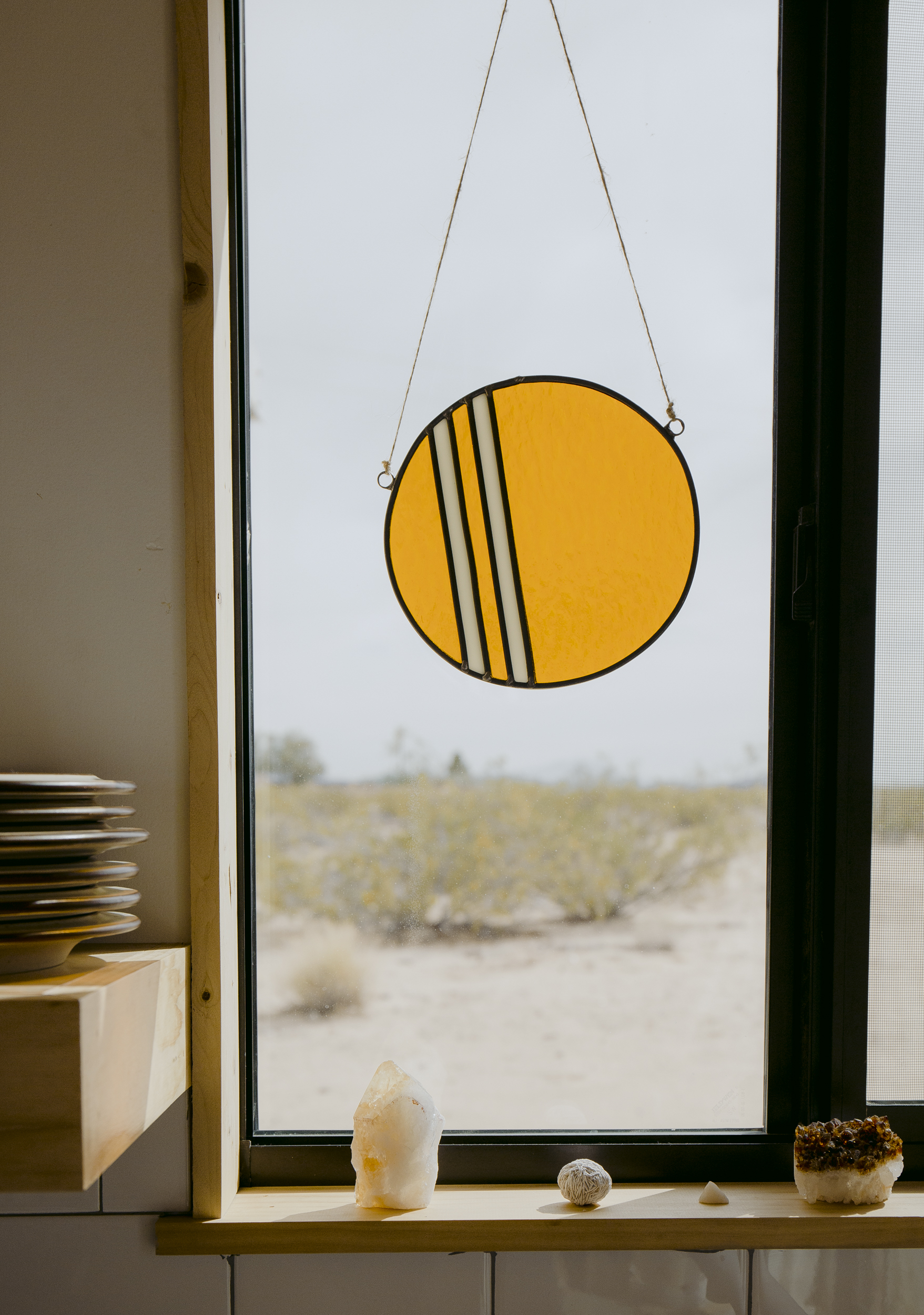 Kathrin's stained Striped Circle in Amber suspends in the kitchen window of her and her husband Brian's Airbnb property The Shack Attack. Her work seamlessly blends with the serene and calm natural tones inside and outside the space. A symbol of the divine power of the sun deep in the heart of the Joshua Tree desert.