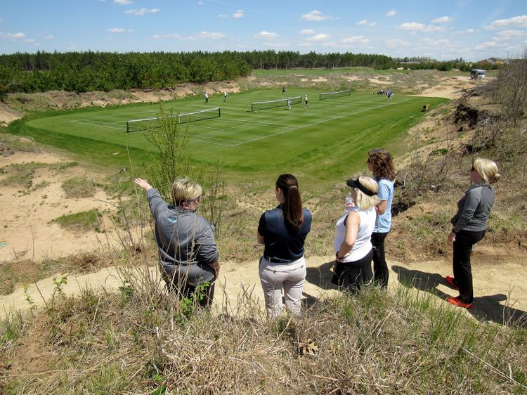 Pam Hammond, left, executive director of the Wisconsin Tennis Association, looks over one of the three-court pitches at Sand Valley Golf Resort in Adams County. The 15 tennis courts are the only public grass courts in Wisconsin. (Image from BARRY ADAMS, STATE JOURNAL)
