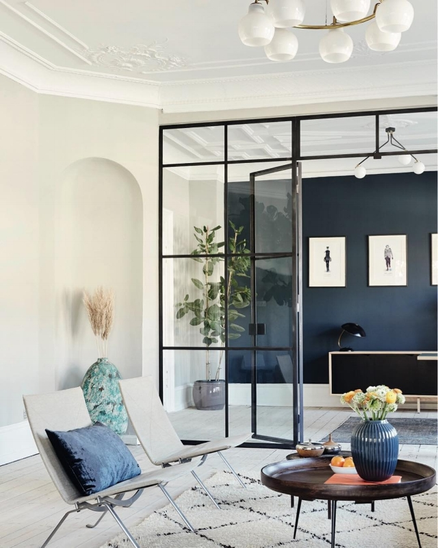 Adding a black frame to the glass panels gives the wall an industrial look that balances well with the very classic interior. Photo by Ditte Capion