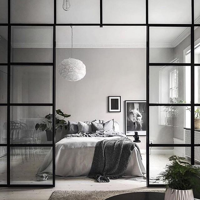The contrast of the soft textures in the bedroom and hardness of the black framed glass wall creates the perfect balance of feminine and masculine. Photo by Kronfoto