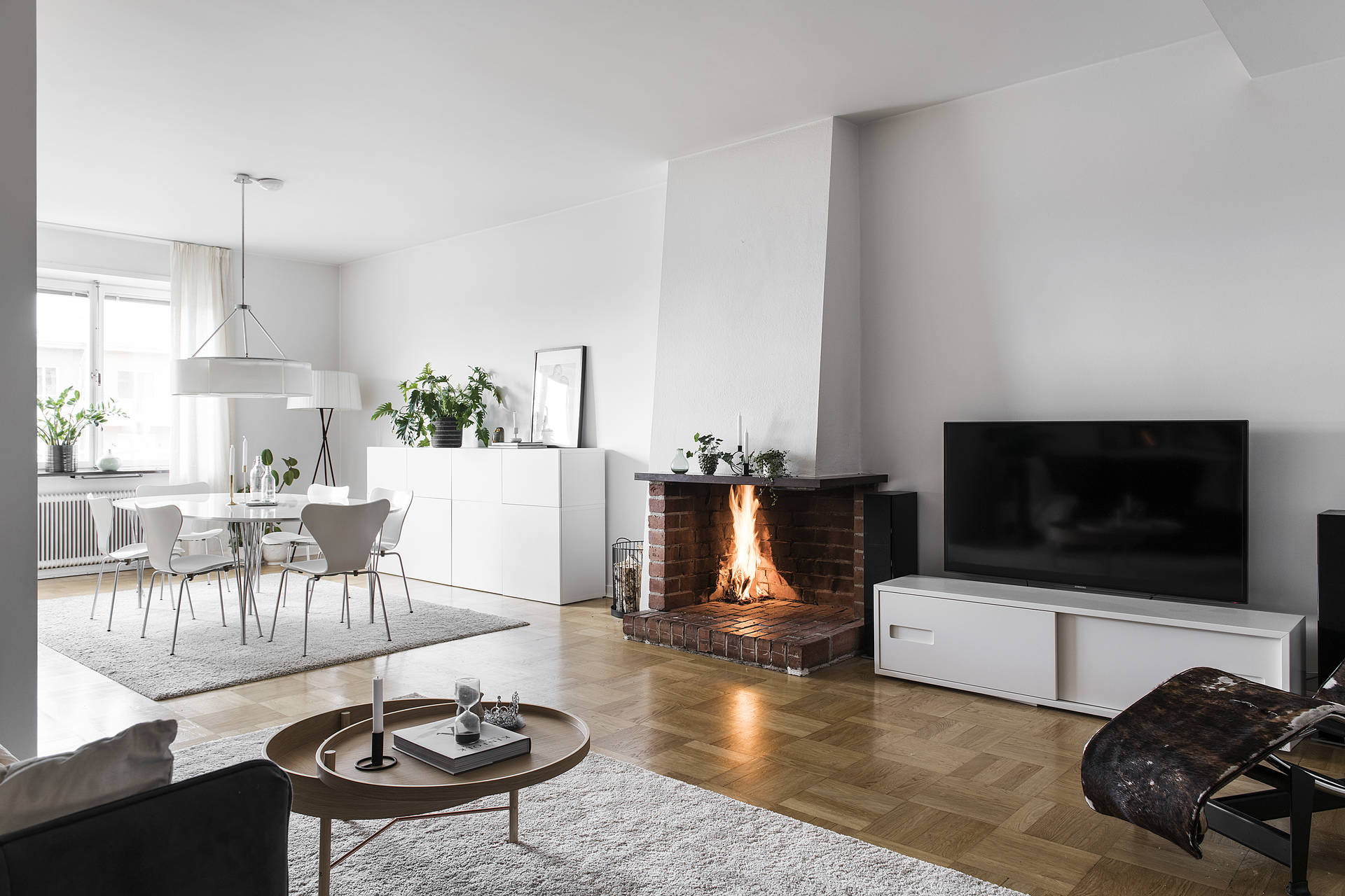 The exposed bricks of the fireplace adds character and warmth to the otherwise cool white interior.