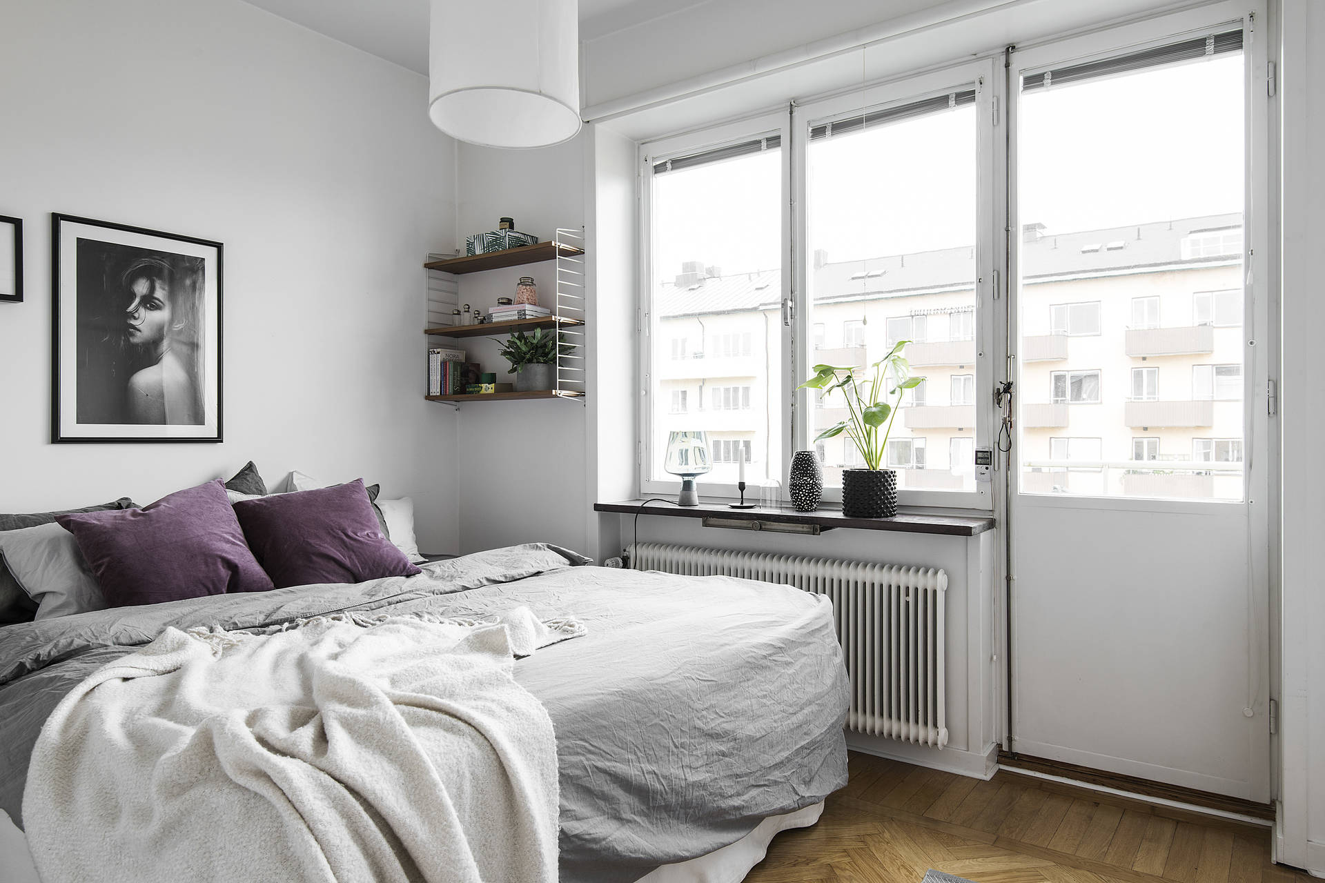 Soft textiles and a touch of purple gives this small master bedroom a very feminine feel.