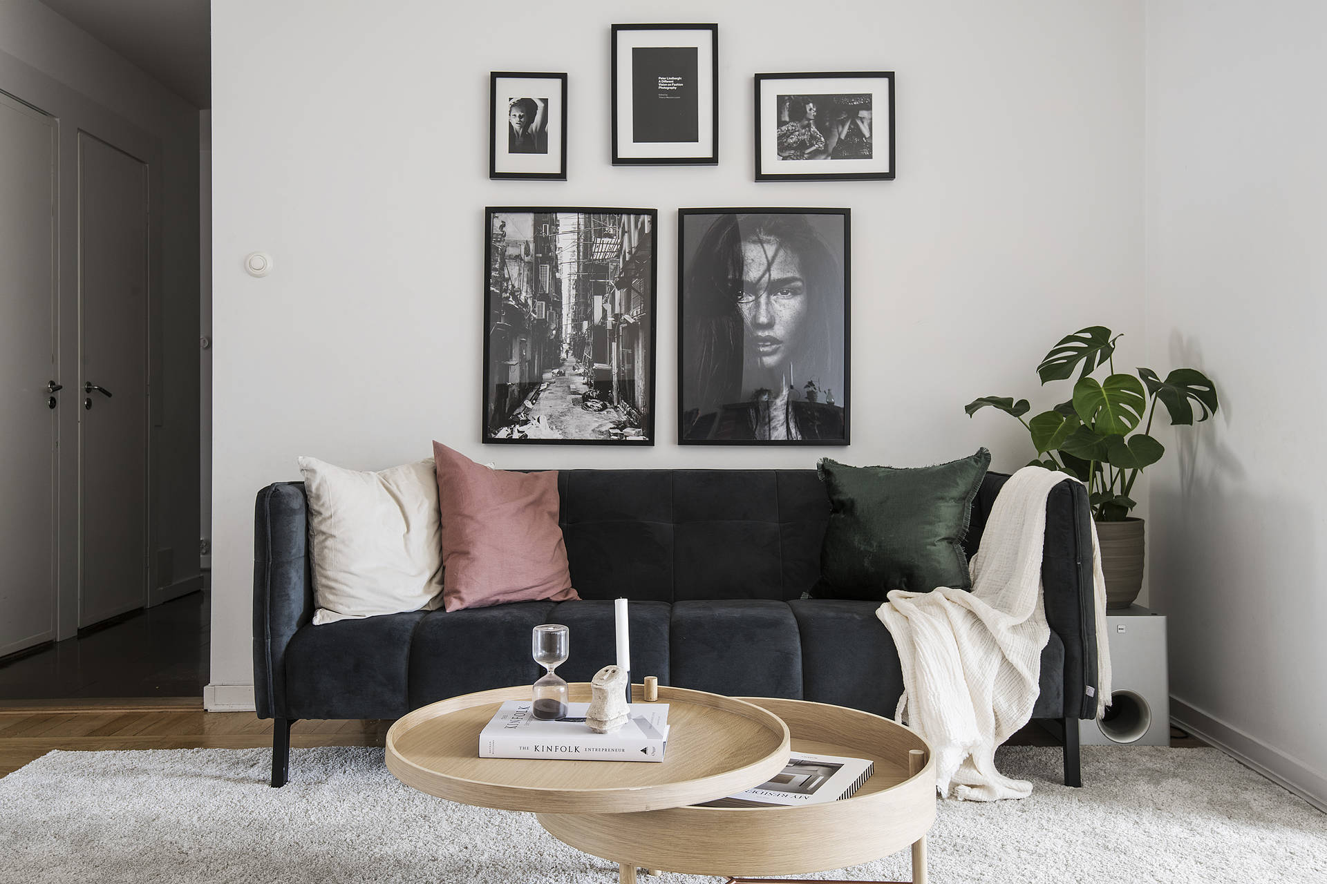 The otherwise monochromatic interior is softened up with wood, green plants and small pops of colour.