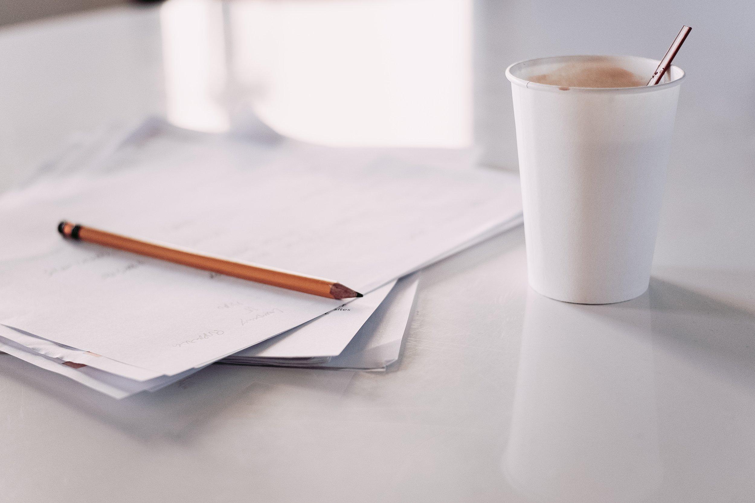 pencil on paper with coffee cup rainier-ridao-569546-unsplash.jpg