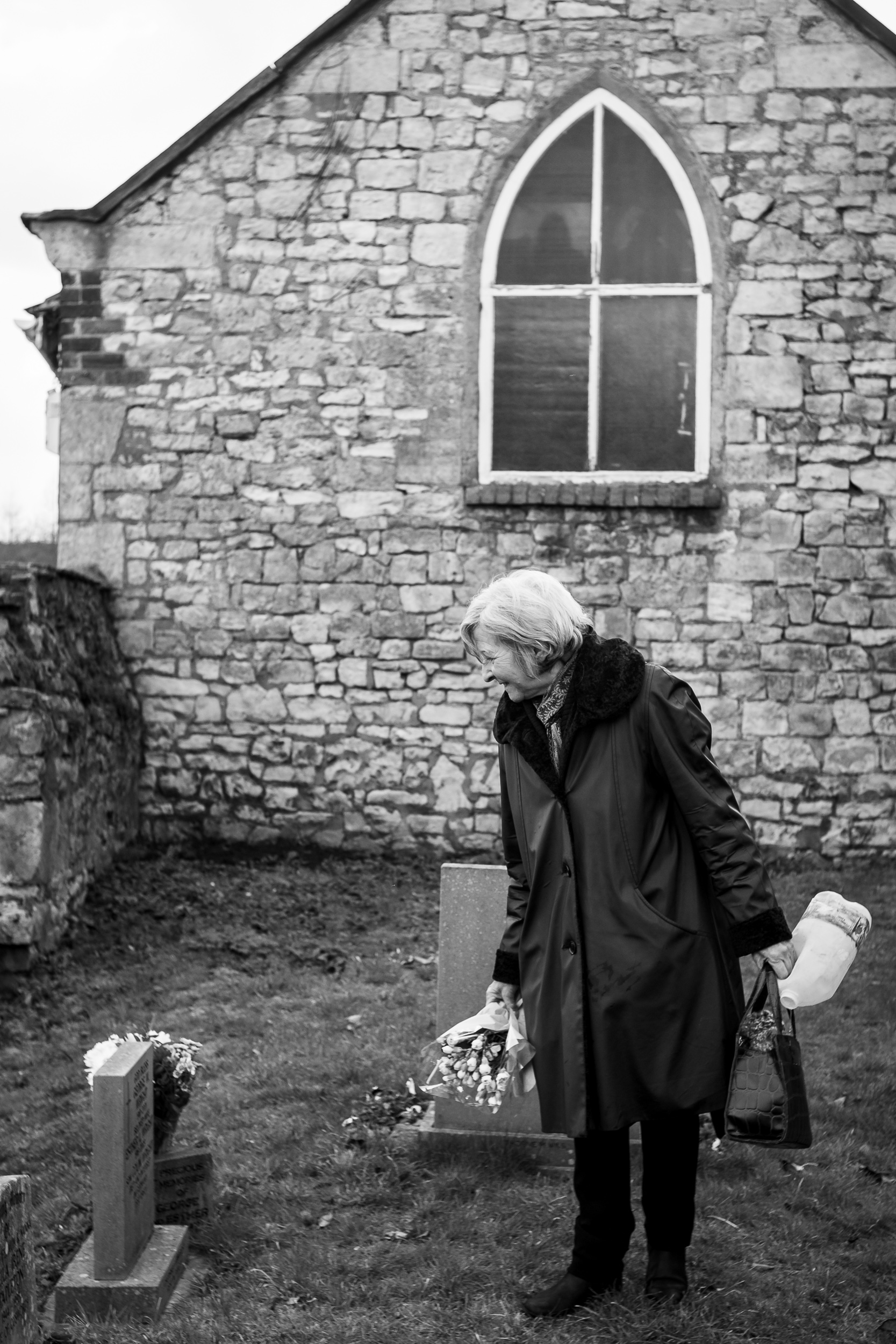 Mum laying fresh flowers on her parents grave