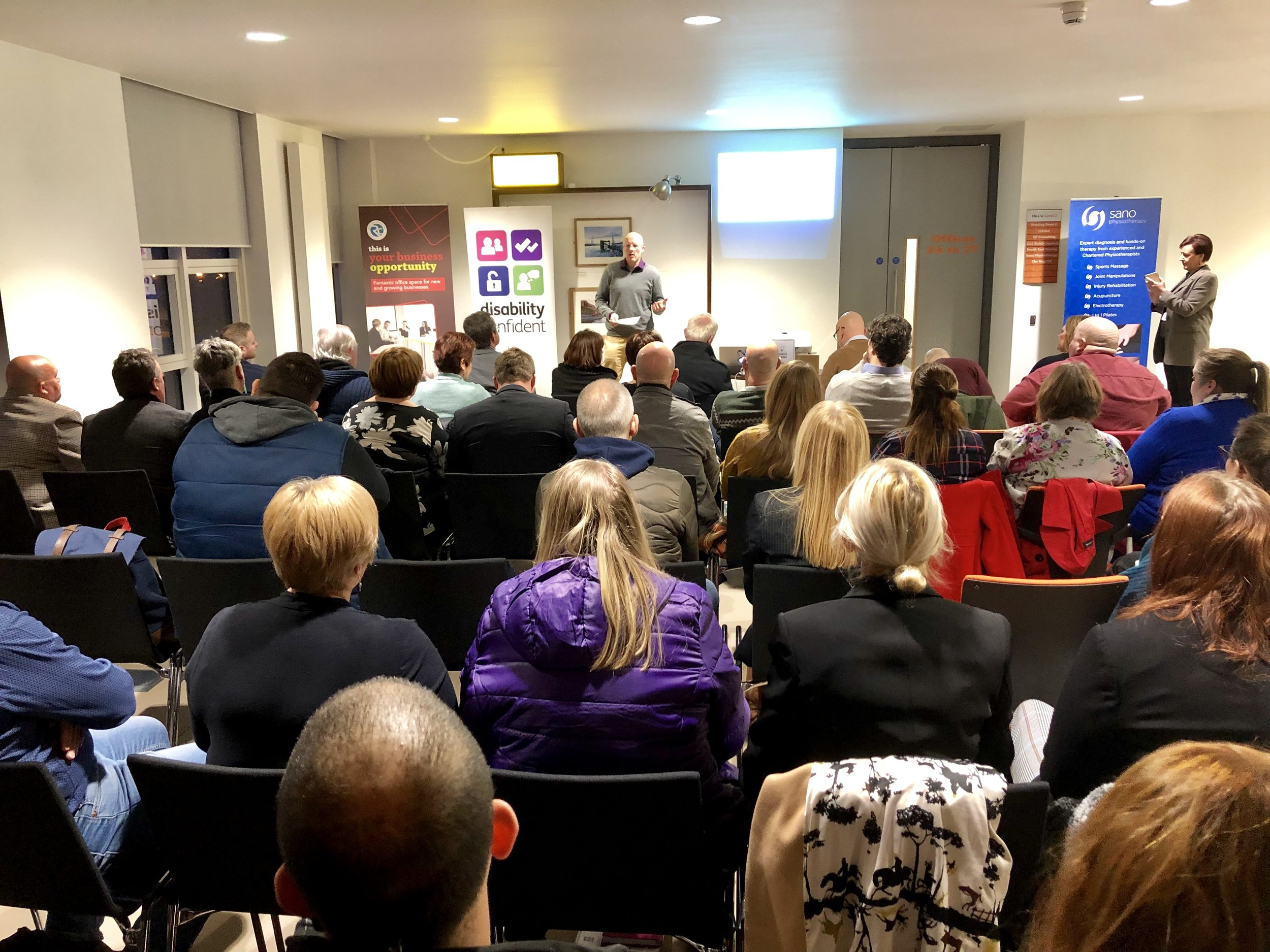 Crowded room of seated people facing Darren Winter from Duco Digital and Karen King from Kings Celebrant Services filming event.