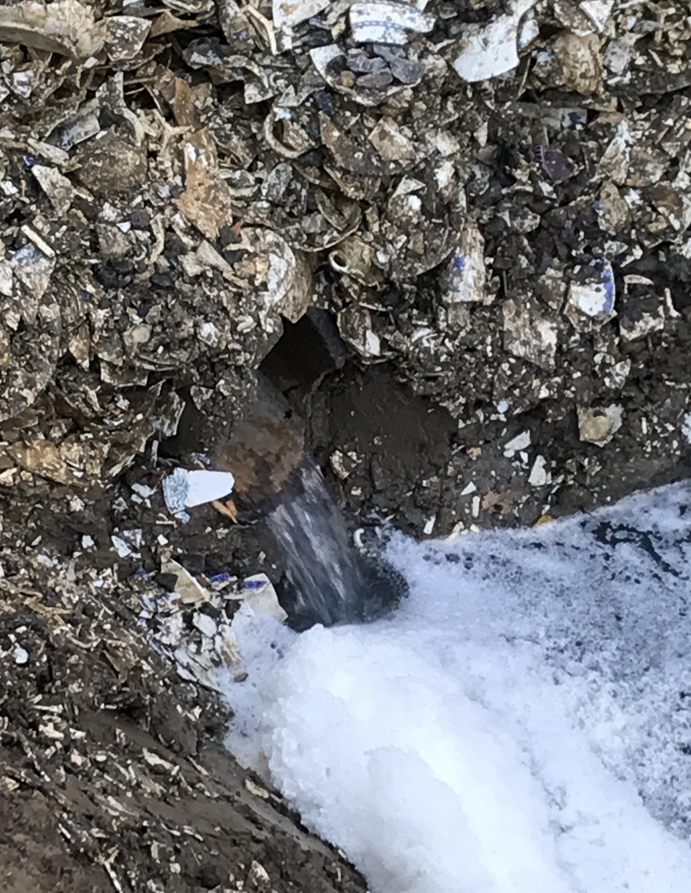 Slutet av cementröret som kommer från V&B:s soptipp och vattnet som rinner ut i stenkistan.
