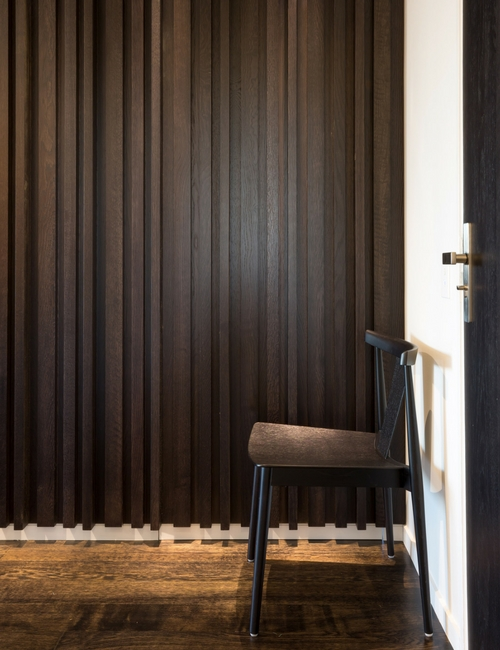 vertical lines - Light peeps out from the striking panelled wall feature.