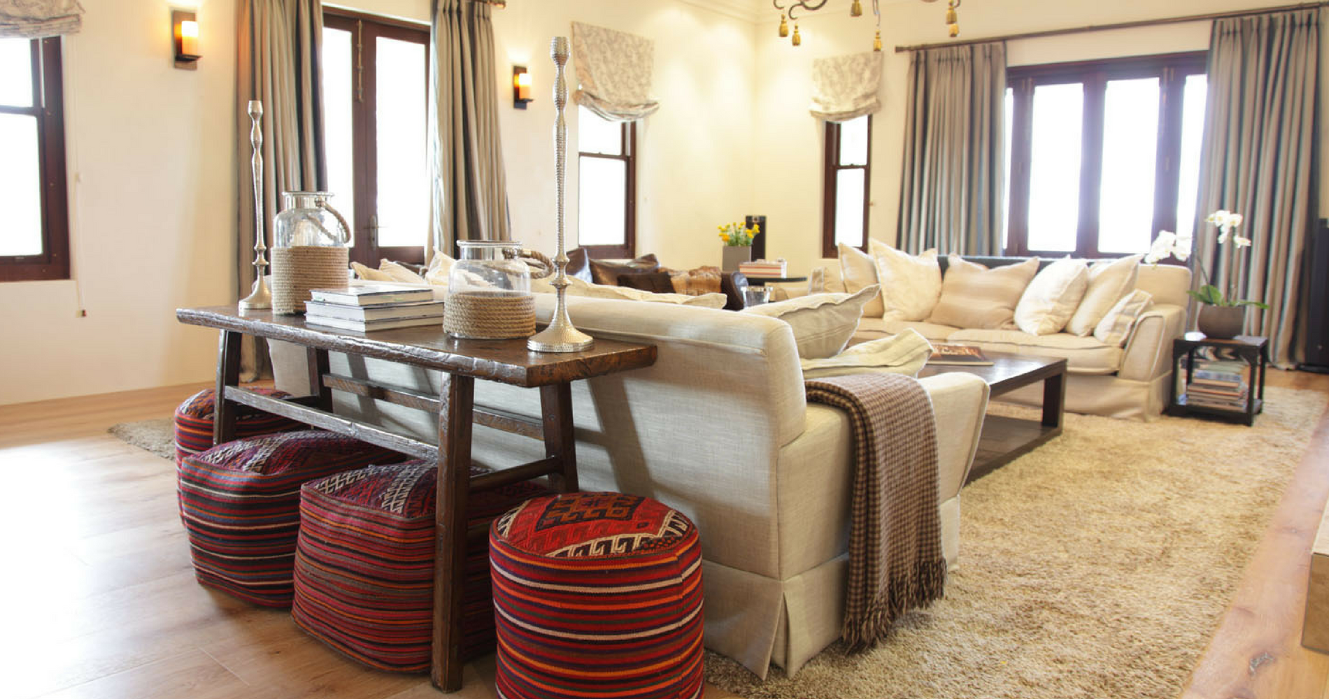 A light-filled open lounge space is made cozy by oversized cushions, woollen throws and unique, brightly coloured ottomans.