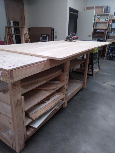 I made my rolling shop table the same height as my table saw, I swear I'll never bend over sawhorses to cut lumber again! Notice the racks for templates and jigs.
