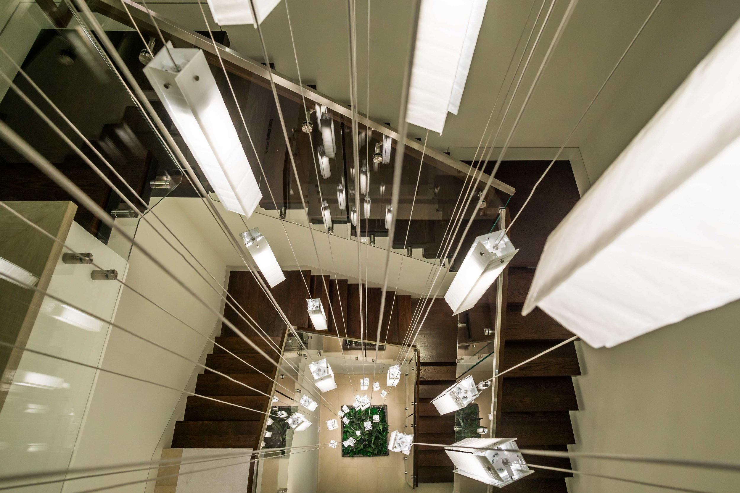 Interior real estate photograph Of Massive Modern minimal chandelier That isThree stories high