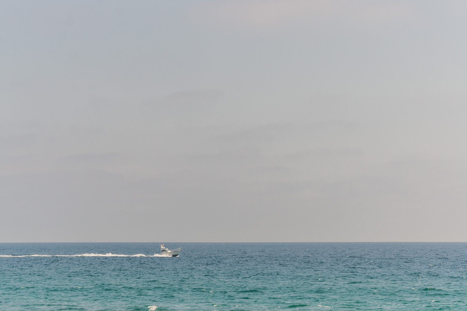 view from Newport Beach pier on a Sunny day overlooking ocean and speed boat