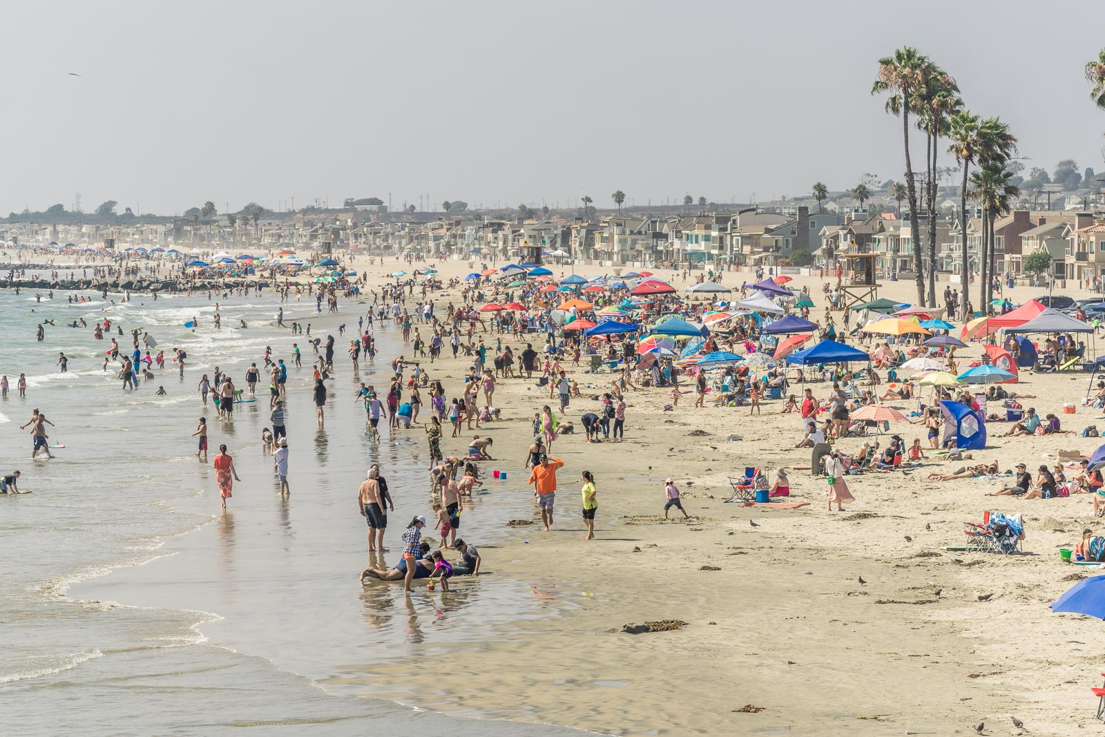 view from Newport Beach pier on a Sunny day overlooking the crowded beach of swimmers